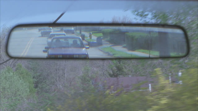 CLOSE ANGLE DRIVING POV IN REAR VIEW MIRROR OF CARS FOLLOWING DOWN STREET IN RESIDENTIAL AREA, NEIGHBORHOOD OR SUBURB. TREES AND MIDDLE CLASS HOUSES, COULD BE COUNTRY ROAD.