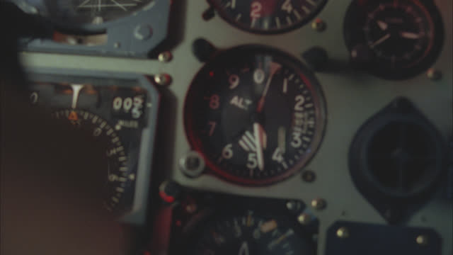 close angle of control or instrument panel of helicopter or airplane. speedometer or airspeed indicator, altitude monitor or altimeter, pressure gauges, magnetic compass, heading indicator, vertical speed indicator, and joystick or controller and hand vis - 計測器点の映像素材/bロール