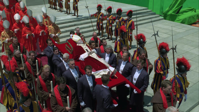 vídeos de stock, filmes e b-roll de high angle down of funeral procession of dead pope. corpse on elaborate platform. priests, cardinals, and men in suits present. procession marches past crowds. green screen in bg. rome. vatican. catholic church. papal regalia. - pope