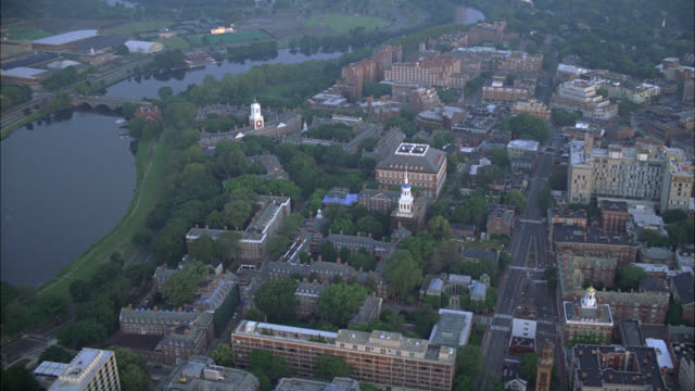aerial of charles river in cambridge, massachusetts near harvard university campus. apartment buildings, dormitories, campus buildings, and university visible. college campuses. ivy league. boston. - river charles stock videos & royalty-free footage