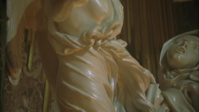 PAN UP FROM FOOT OF MARBLE SCULPTURE OR STATUE ILLUMINATED BY REFLECTION OF FLAMES OR FIRE TO MEDIUM ANGLE OF 'ECSTASY OF SAINT THERESA STATUE.' STATUE IN CORNARO CHAPEL IN SANTA MARIA DELLA VITTORIA IN ROME. STATUE OF WOMAN WITH ANGEL HOLDING ARROW. RELI