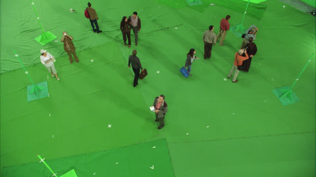HIGH ANGLE DOWN OF PEOPLE OR TOURISTS STANDING ON GREEN SCREEN STAGE. PEOPLE LOOK ALL AROUND AND READ PAMPHLETS. COULD BE USED FOR MUSEUM.