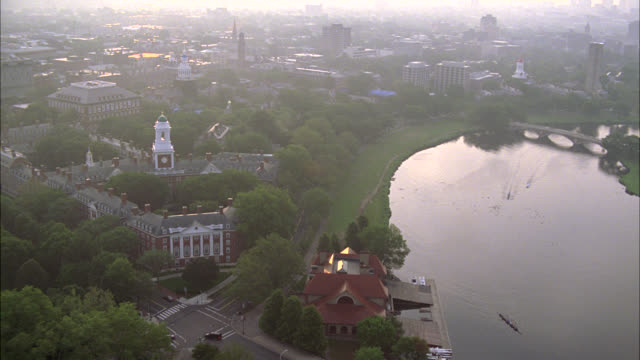stockvideo's en b-roll-footage met aerial of charles river in cambridge, massachusetts near harvard university campus. apartment buildings, dormitories, campus buildings, and university visible. college campuses. ivy league. boston. - harvard university