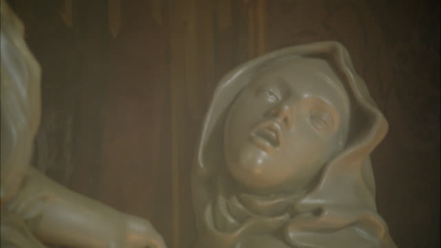 CLOSE ANGLE OF MARBLE SCULPTURE OR STATUE ILLUMINATED BY REFLECTION OF FLAMES OR FIRE. CLOSE ANGLE OF 'ECSTASY OF SAINT THERESA STATUE.' STATUE IN CORNARO CHAPEL IN SANTA MARIA DELLA VITTORIA IN ROME. STATUE OF WOMAN WITH ANGEL HOLDING ARROW. RELIGIOUS AR