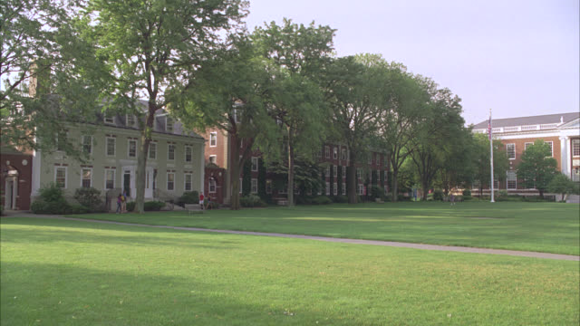 stockvideo's en b-roll-footage met wide angle of harvard campus and central green. trees surround property and university buildings. college campus. ivy league. students walk around campus. could be apartment buildings, faculty housing, or student housing in bg. boston. - harvard university