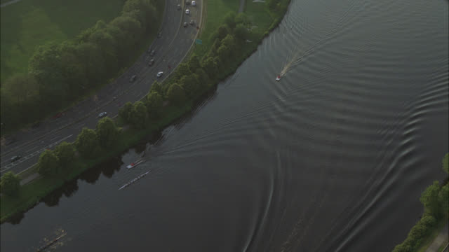 aerial of administration buildings on harvard campus. college or university. ivy league. building has tower and spire. trees surround campus. boats in charles river leaving wake. rowing or crew. boston. - 米マサチューセッツ州 ケンブリッジ点の映像素材/bロール