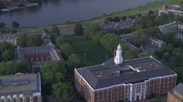 stockvideo's en b-roll-footage met aerial of administration buildings on harvard campus. college or university. ivy league. building has tower and spire. trees surround campus. boats in charles river leaving wake. rowing or crew. boston. - harvard university