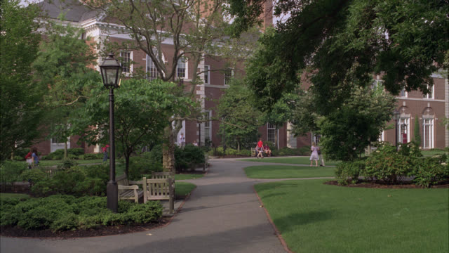 stockvideo's en b-roll-footage met wide angle of walkways or sidewalk on harvard university campus. college. students walk around. building in bg. trees surround property. bench and light post. boston. ivy league. - harvard university