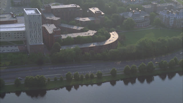 stockvideo's en b-roll-footage met aerial of administration buildings on harvard campus. college or university. ivy league. building has tower and spire. trees surround campus. boats in charles river leaving wake. rowing or crew. football stadium visible. - harvard university