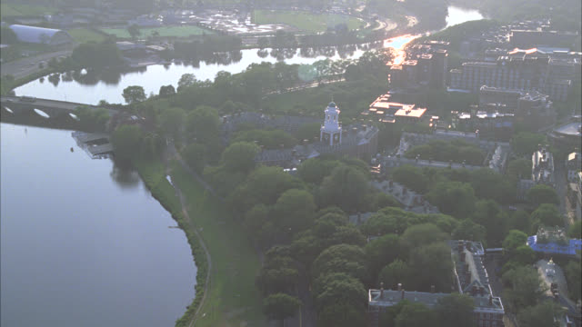 aerial of administration buildings on harvard campus. college or university. ivy league. new england. building has tower and spire. trees surround campus. charles river. boston. - 米マサチューセッツ州 ケンブリッジ点の映像素材/bロール