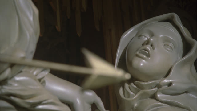 "close angle of marble sculpture or statue. close angle of ""ecstasy of saint theresa statue."" statue in cornaro chapel in santa maria della vittoria in rome. statue of woman with angel holding arrow. religious art. catholic. - statuetta video stock e b–roll"