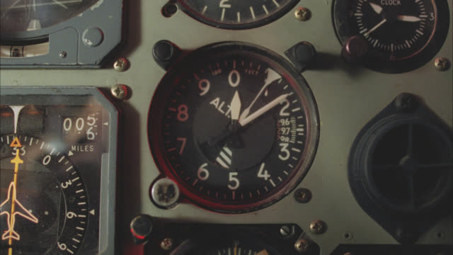 close angle of control or instrument panel of helicopter or airplane. speedometer or airspeed indicator, altitude monitor or altimeter, pressure gauges, magnetic compass, heading indicator, vertical speed indicator. camera focuses on altimeter gauge spinn - 計測器点の映像素材/bロール