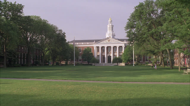 stockvideo's en b-roll-footage met wide angle of harvard campus and central green. trees surround property and university buildings. college campus. building in bg with pillars or columns and tower with spire. ivy league. students walk around campus. boston. - harvard university