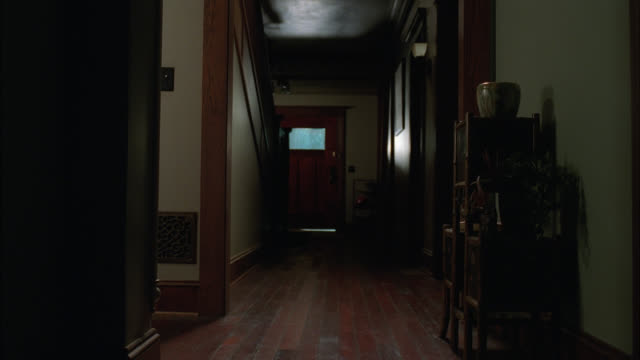 vídeos de stock, filmes e b-roll de medium angle of hallway in middle class home. wood floors and shelves visible. front door with window visible. rain and lightning outside. could be storm. entryway. - átrio interior de casa