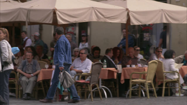 stockvideo's en b-roll-footage met wide angle of people sitting and eating at outdoor cafe or restaurant. large umbrellas. pedestrians walk around on cobblestone street. rome. vatican. - rome italië