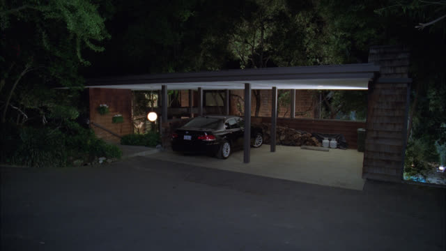 wide angle of car port attached to house. car parked under car port. fire wood and propane tanks visible. lights. driveways. - driveway stock videos & royalty-free footage
