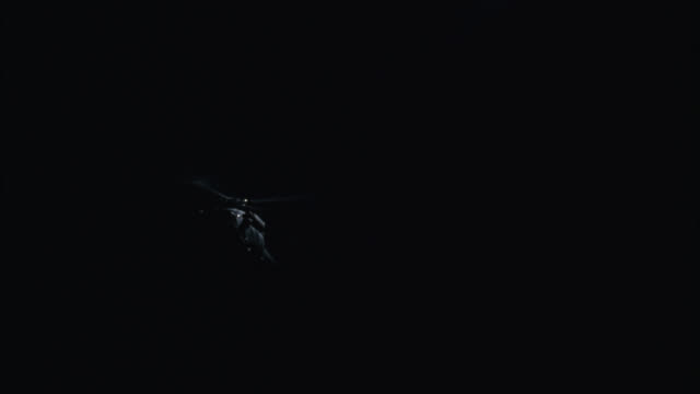 up angle of military helicopters flying in sky. search lights. - military helicopter stock videos & royalty-free footage