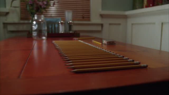 close angle of sharpened pencils in a line or row on table. - pencils in a row stock videos & royalty-free footage