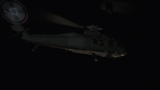 pan up of military helicopter taking off into sky. bare branches of trees in woods or forest in bg. - military helicopter stock videos and b-roll footage