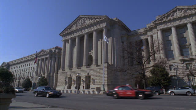 WIDE ANGLE OF GOVERNMENT BUILDING WITH PILLARS AND BAS RELIEF ABOVE ENTRANCE. COULD BE CONSULATE, COURTHOUSE, OR CITY HALL. FLAG ON FLAGPOLE IN FRONT OF BUILDING. CARS DRIVE BY ON STREET.