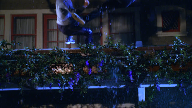 stockvideo's en b-roll-footage met pan down of two men falling from rooftop. two story middle class house. flowers, vines. rain, storm. lightning. stunt. could be during accident or fight. - men