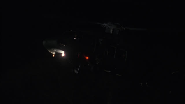 pan down of military helicopter landing in field in front of two story upper class house or mansion. brick manor or estate with many chimneys. flashing lights on bizbars of fire trucks or engines, ambulances and police cars. could be crime scene or emerge - military helicopter stock videos and b-roll footage