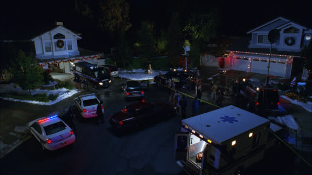 high angle down of crime scene in residential area or neighborhood cul-de-sac. ambulances, police cars, and medical examiner van visible. police tape. christmas lights and decorations on houses. snow in front yards. could be murder. flashing lights or biz - crime stock videos & royalty-free footage