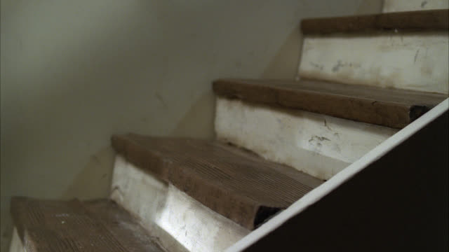 close angle of elderly woman falling down basement steps. stunts. - andare giù video stock e b–roll