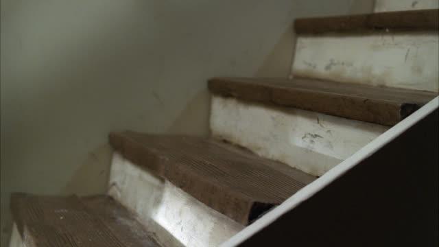 close angle of elderly woman falling down basement steps. stunts. - scale video stock e b–roll