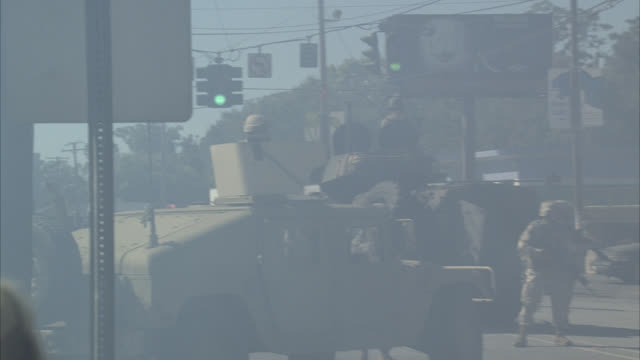 wide angle of military or army personnel in armored tank and hummer parked on street corner. haze or smoke lingers in air. store and billboard visible in bg. traffic lights. soldiers gesture for someone or multiple someone's to come towards them. could be - army stock-videos und b-roll-filmmaterial