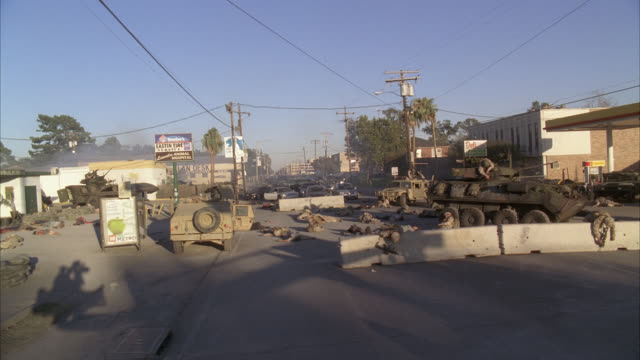 wide angle moving pov right to left of  city street strewn with dead bodies of soldiers and civilians. gas station in fg. tank and military hummer visible. barricade in fg. could be attack or disaster. shops, storefronts, and restaurants line street. - hummer stock videos & royalty-free footage