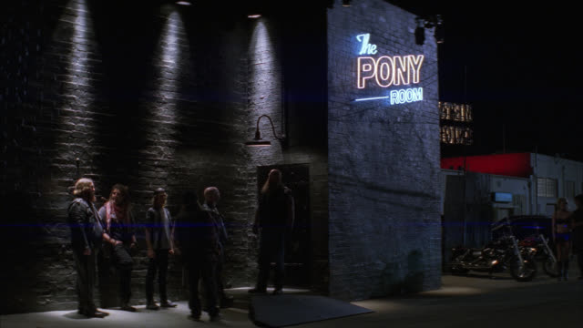 wide angle of patrons standing outside bar with sign on brick building reading 'the pony room.' motorcycles parked outside entrance. could be motorcycle bar or lower class bar. bouncer at door. - motorcycle biker stock videos & royalty-free footage