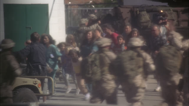 wide angle from pov of inside of bus of people panicking and being evacuated on city street by police officers, fire fighters, and military in city street. could be army. soldiers armed in tanks and wearing camo. smoke lingers in air. people running and a - army stock-videos und b-roll-filmmaterial