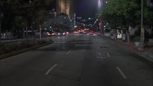 wide angle moving pov of cars driving on wilshire blvd. wiltern theater vertical marquee visible in bg. buildings line street. bus stop waiting area visible. cars drive in both directions. - wiltern theater stock videos & royalty-free footage