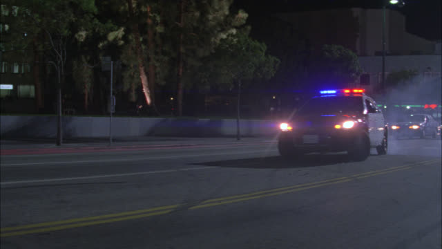 vídeos y material grabado en eventos de stock de wide angle moving pov of police car making sharp u-turn on wilshire boulevard into oncoming traffic. cars driving. police car swerves with flashing lights or bizbar. could be car chase. - coche de policía