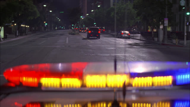 wide angle moving pov from top of police car driving down wilshire boulevard. bizbar in fg. wiltern theater marquee visible in bg. cars driving in both directions. police car makes sharp u-turn into oncoming traffic and with lights flashing pursues car in - wilshire boulevard stock videos & royalty-free footage