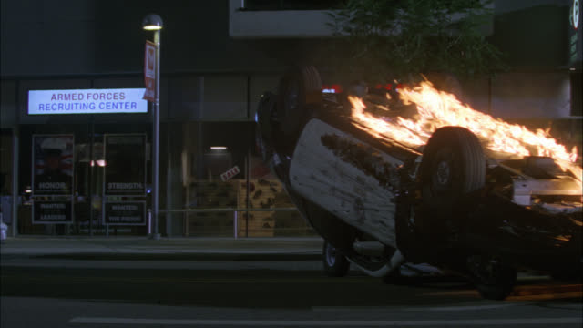 "medium angle of overturned police car on fire in middle of city street. storefront or shop in bg for shoes and 'armed forces recruiting center."" could be accident, crash, or collision. - police car stock videos & royalty-free footage"