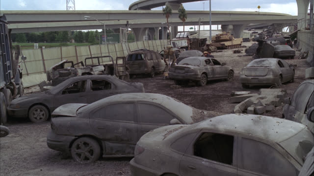 wide angle of freeway with cars covered in ash. destruction. alien. could be aftermath of attack or natural disaster. could be apocalyptic. actually louisiana. army or military tank in bg. overpasses. - kampfpanzer stock-videos und b-roll-filmmaterial