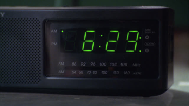 CLOSE ANGLE OF ALARM CLOCK RADIO CHANGING FROM 6:29 TO 6:30. DIGITAL DISPLAY.