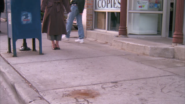TRACKING SHOT OF MAN'S FEET AND LEGS WALKING ON SIDEWALK. MAN GRABS WOMAN. COULD BE A MUGGING. PEOPLE, PEDESTRIANS.