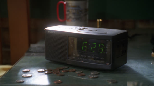 stockvideo's en b-roll-footage met pull back from alarm clock radio on nightstand. change or coins. - electrical equipment