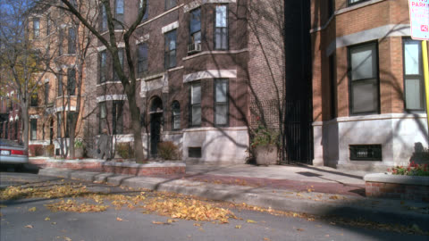 wide angle of multi-story brick apartment buildings. city street. people or pedestrians on sidewalk. wind blowing dry leaves. - 階点の映像素材/bロール
