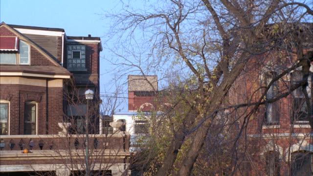 wide angle of el train on tracks between two brick houses. trees in fg. - れんが造りの家点の映像素材/bロール