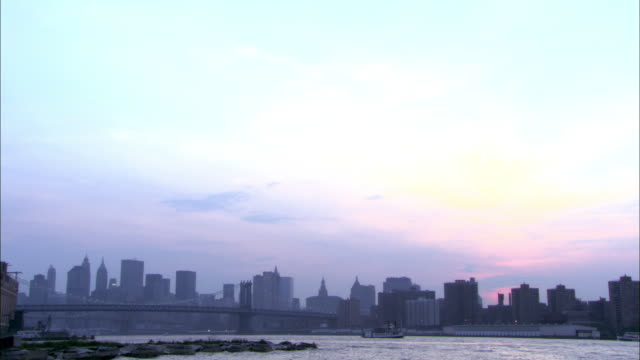 pan down to the new york city skyline, the manhattan bridge over the east river, the skyscrapers and office buildings of lower manhattan in the distance.  a boat floats uptown. - 2007年点の映像素材/bロール