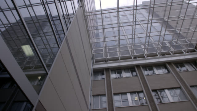 up angle of glass high rise office building atrium. could be hospital atrium. camera pans from left to right and right to left. camera also pans up and down to the lobby below. - lobby stock videos & royalty-free footage