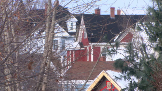medium angle of neighborhood with upper or middle class two story houses. camera zooms in on red brick house then zooms out and pans right to left. camera focuses on  porch and snow covered roof with icicles of another house. - brick house stock videos & royalty-free footage