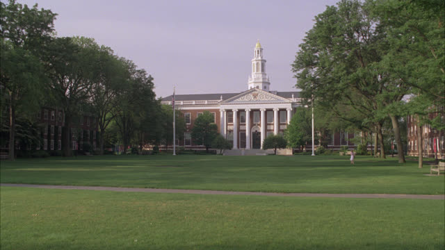 wide angle of harvard campus and central green. trees surround property and university buildings. college campus. building in bg with pillars or columns and tower with spire. ivy league. students walk around campus. boston. - harvard university stock videos & royalty-free footage