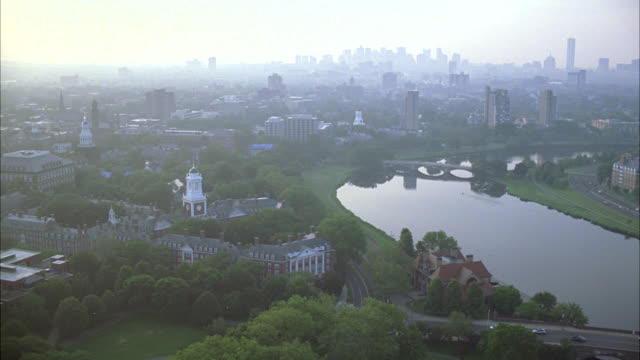 AERIAL OF CHARLES RIVER IN CAMBRIDGE, MASSACHUSETTS NEAR HARVARD UNIVERSITY CAMPUS. APARTMENT BUILDINGS, DORMITORIES, CAMPUS BUILDINGS, AND UNIVERSITY VISIBLE. COLLEGE CAMPUSES. IVY LEAGUE. BOSTON.