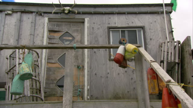 vidéos et rushes de medium angle of fishing shack or boathouse. heavily used fishing gear hangs from  staircase railing. - cahute