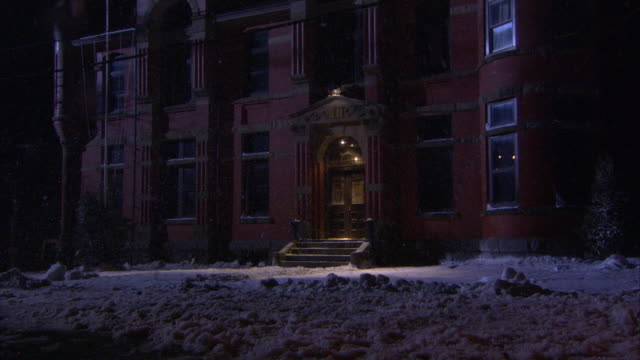 wide angle of red brick two story building. a 1959 light blue ford fairlane pulls up to  front of the building. camera pans up to capture the facade of  building. could be a school,  hospital, orphanage, or upper class house. power lines.  snow. blizzard. - orphanage stock videos and b-roll footage